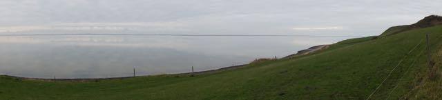 De Krik Vig, inham van de Limfjord waar het Gele Huis aan ligt, weerspiegelt de grijze lucht