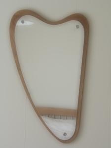 De spiegel in de slaapkamer van het houten vakantiehuis. Lijkt dit op een harp op niet?