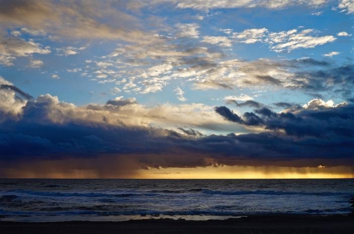 Aan het eind van een mooie zomerdag. Regen op zee, verlicht door de ondergaande zon