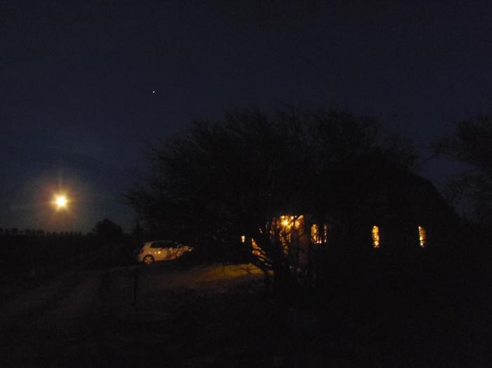 Sfeervol verlicht boerderijtje met volle maan