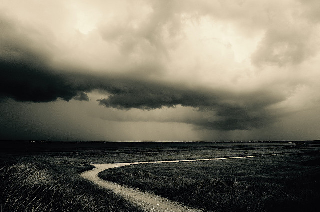Donkere wolken boven een slingerend landweggetje