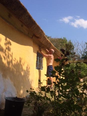 De schade aan de muur onder de dakrand wordt hersteld door metselaar Jacob